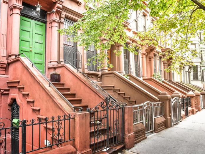 Main ladder and entry door. New york Harlem buildings. Brown houses. NYC, USA.