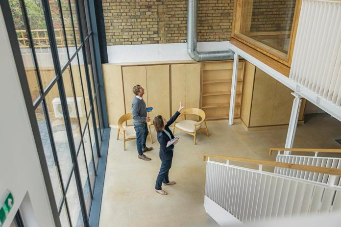 Female property agent showing man around empty office space
