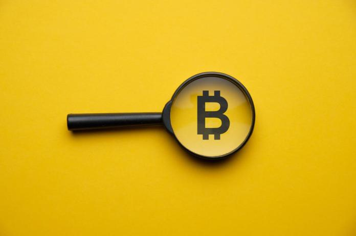 Bitcoin cryptocurrency search concept with magnifying glass on a yellow background.