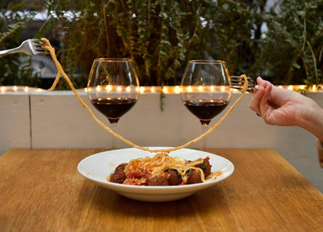 a plate of spaghetti meatballs, two glasses of wine in a recreation of lady and the tramp