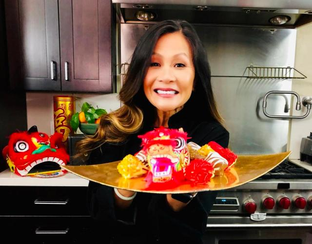 chef katie chin holding gold plate with dragon head and party decorations