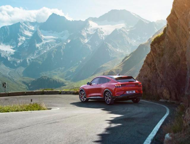 Rear three-quarter view of a red Ford Mustang Mach-E on a mountain road