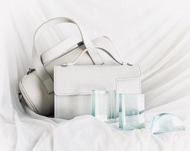 two white leather bags with handles