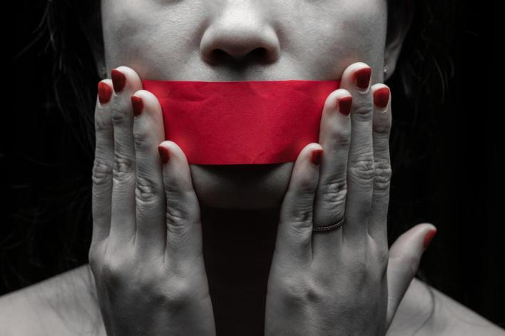 a woman with red tape over her mouth