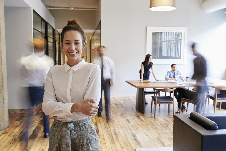 Portrait of young woman in a busy modern workplace