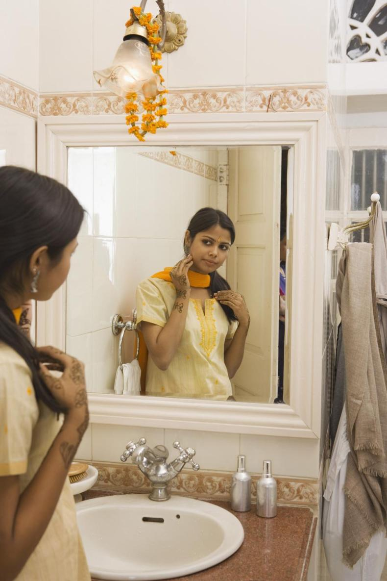 Young adult woman looking at bindhi in mirror.