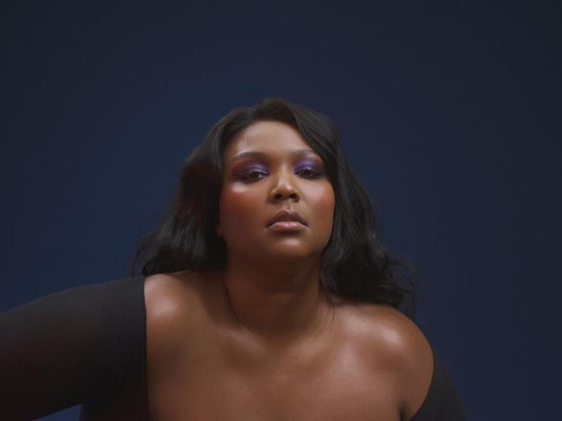Lizzo in a black shirt and purple eyeshadow.