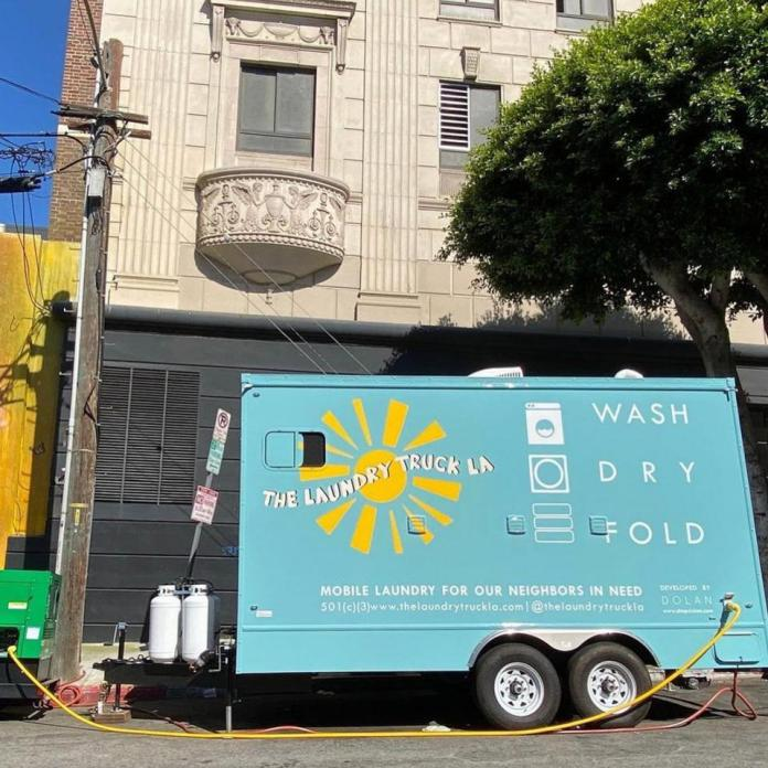 An Aqua Laundry Truck With A Sun On It That Says ″The Laundry Truck La″