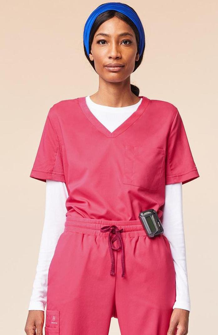 A Black Woman Wearing Red Scrubs And A Blue Headband.