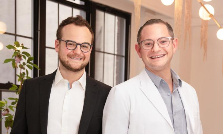 Clearing cofounders Avi Dorfman and Dr. Jacob Hascalovici smiling in front of a window