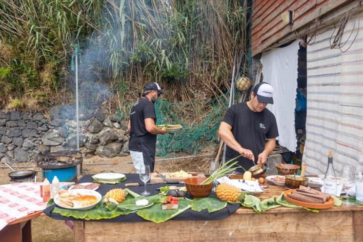 Chefs are cooking lunch over fire as part of a gourmet experience in São Miguel, Azores.