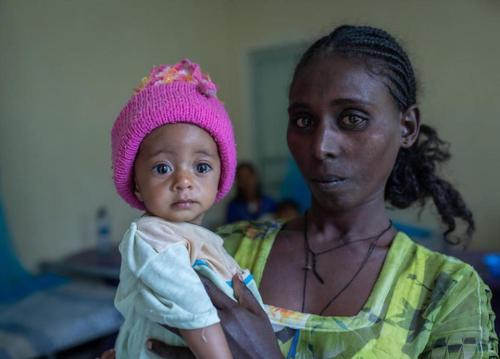 Yeshialem Gebreegziabher, 27, holds her 6-month-old daughter, Kalkidan Yeman, who is suffering from malnutrition, at Aby Adi Health Center in the Tigray region of northern Ethiopia, on June 7, 2021.