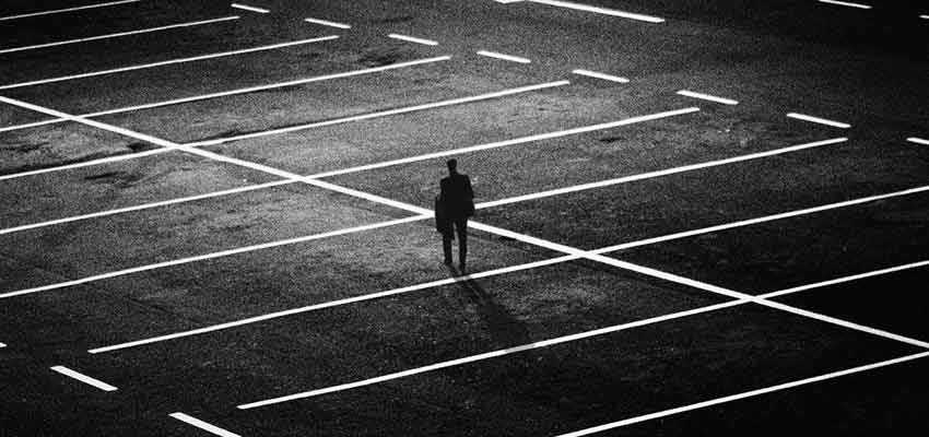 Person standing alone in a dark parking lot.