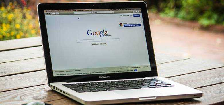 A MacBook Pro displaying the Google home page.