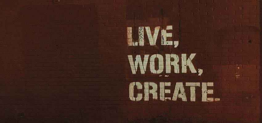 """A wall with the words """"Live, Work, Create"""" painted on it."""