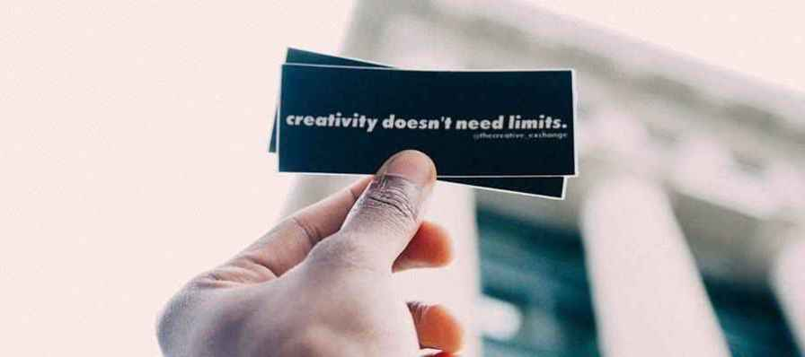 """Person holding a sticker that reads """"creativity doesn't need limits""""."""