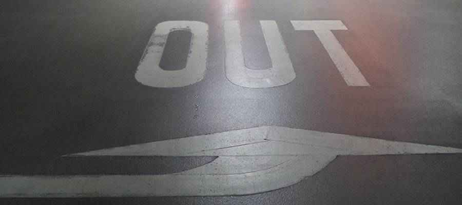 """The word """"OUT"""" painted on a road."""