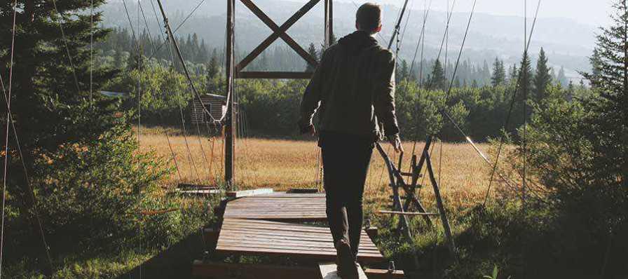 A person walking across a bridge.