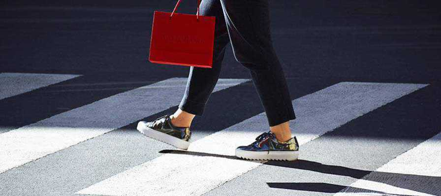 A person walking with a shopping bag.