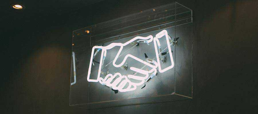 A neon sign depicting a handshake.