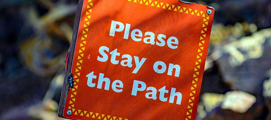 "A sign that reads, ""Please Stay on the Path""."