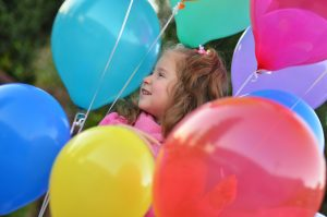 child holds balloons to illustrate autism spectrum disorder blog post