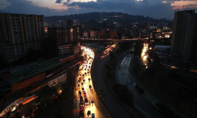 March 9th, 2019 aerial photograph of Caracas, Venezuela showing dark streets lit by car headlights during power outage.