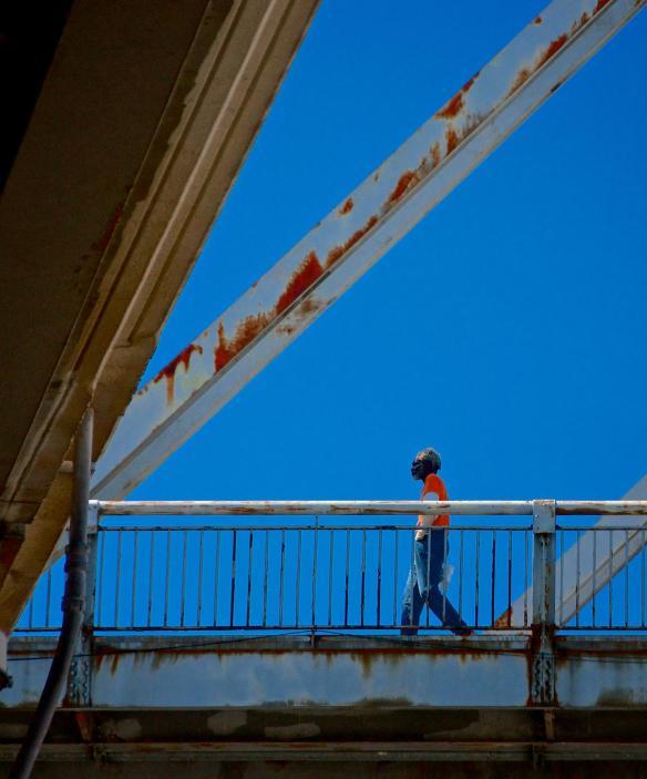 Tight shot of a man Strolling along the Clark Memorial Bridge in Louisville Kentucky
