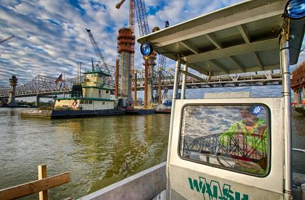 Alan VanWinkle pilots the Walsh crew boat past the towboat Kathleen O'Hara and the Towers at Pier 5 of the Ohio River Bridges Project.