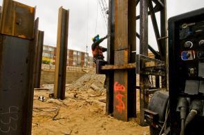 Carpenter climbing pile driver to set hammer.
