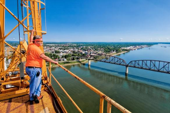 """Marcus """"BigIron"""" Jone Operating Engineer on tower four tower crane deck looking east upriver on the Ohio River."""