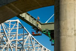 Ironworkers setting a floor beam for the downtown span #3
