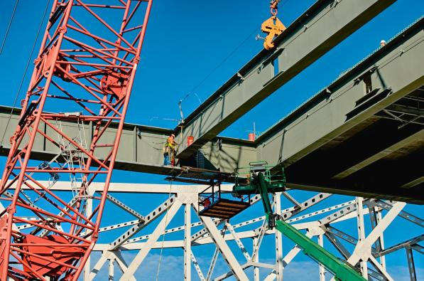 Ironworkers setting a floor beam for the downtown span #2