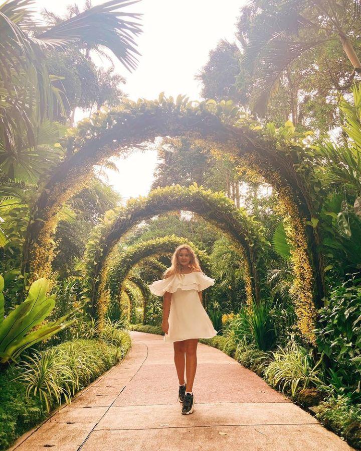 spellbound travels girl walking through singapore botanic gardens