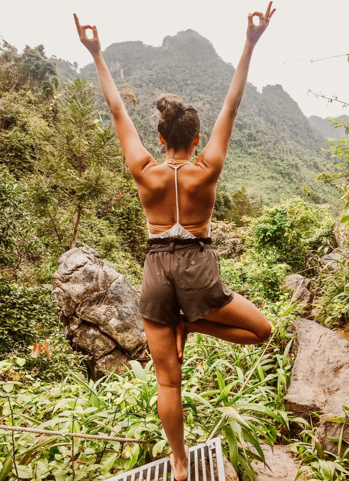 spellbound travels yoga girl posing on top of mountain
