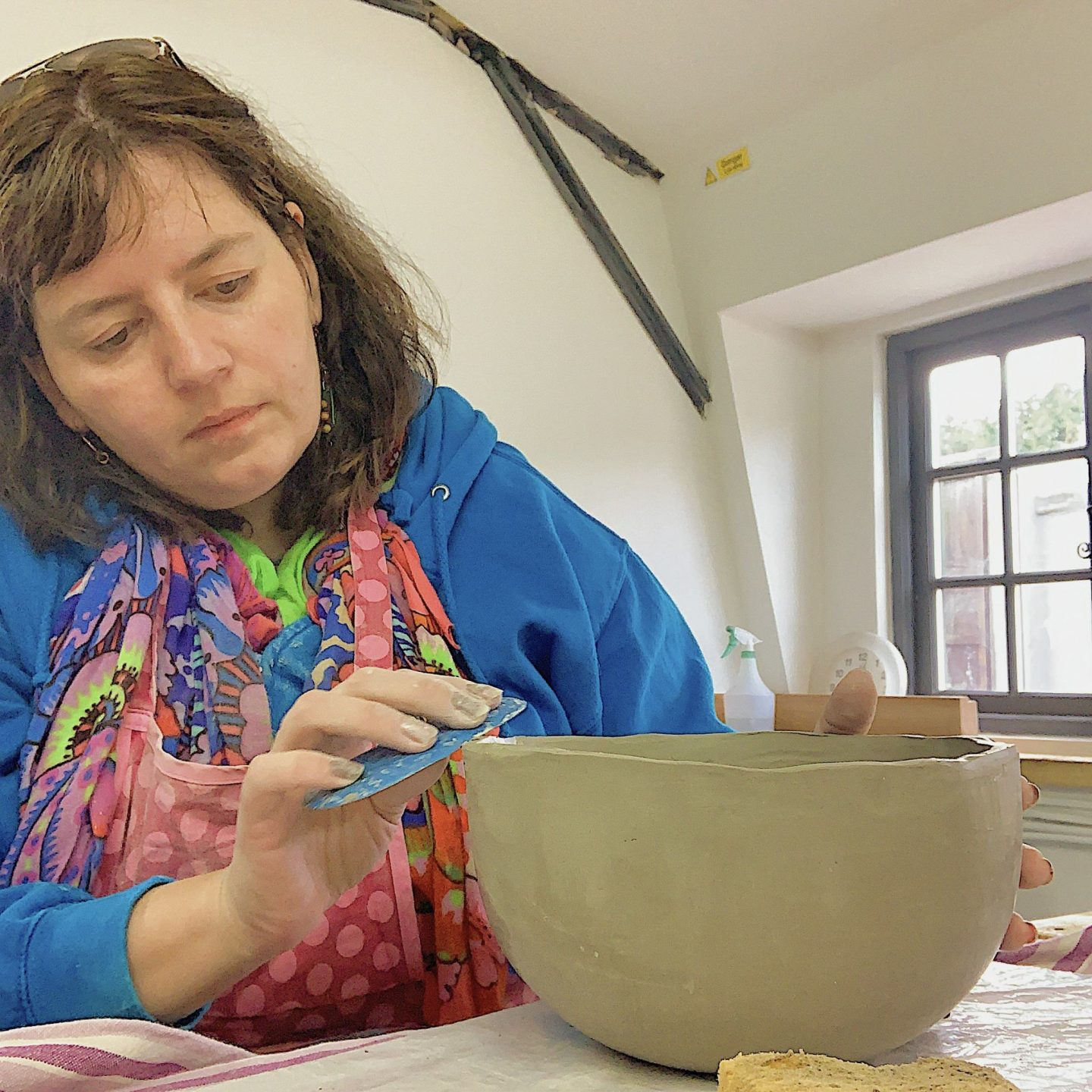 Lady smoothing a ceramic bowl wearing a blue hoody and colourful scarf