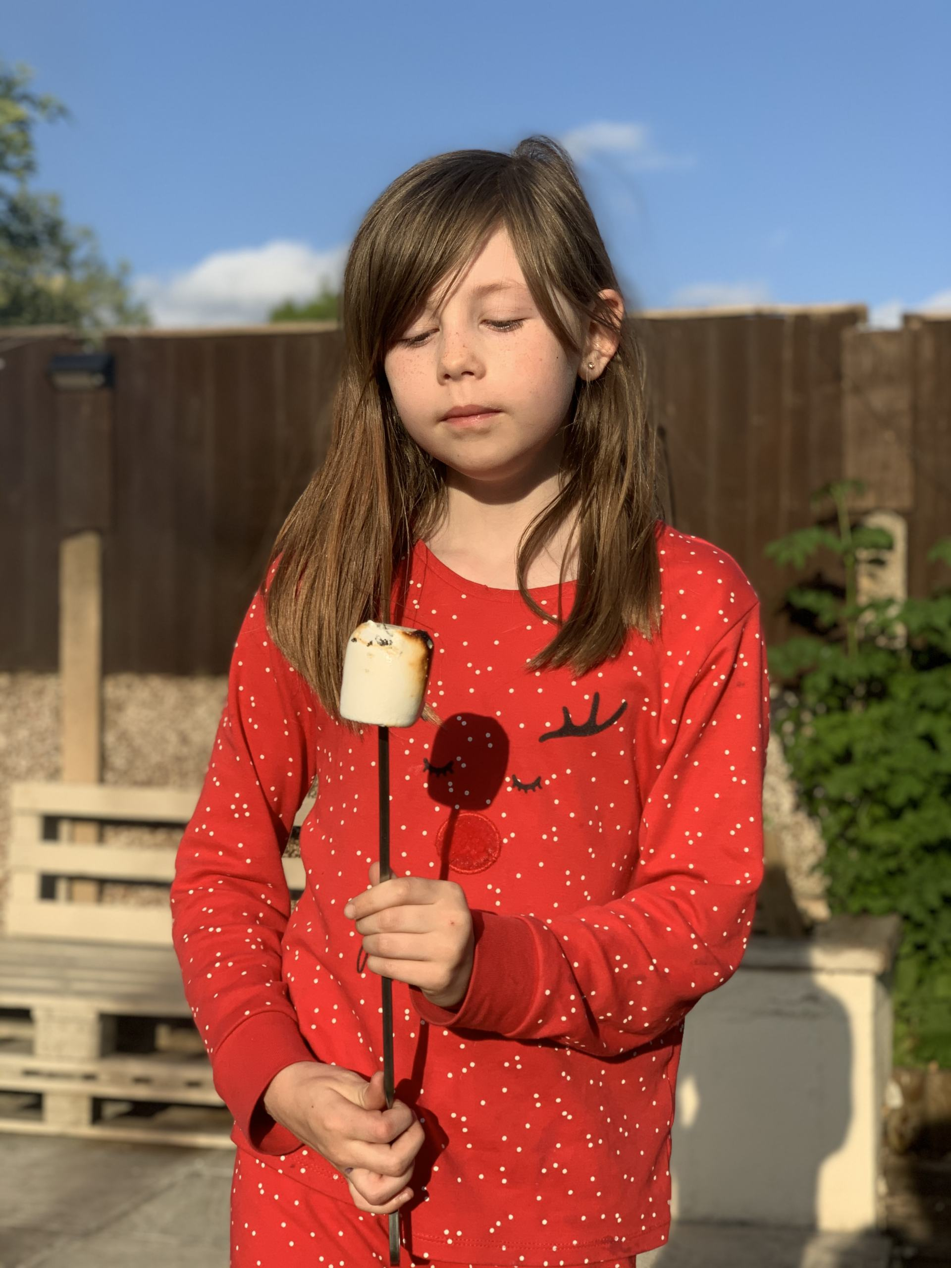 8 year old girl staring at a toasted marshmallow outside with blue sky behind her