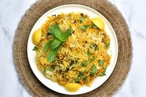 Indian spiced chicken and rice pilaf called chicken biryani served on a white plate.