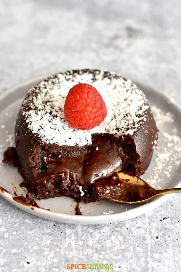 Melted chocolate lava cake topped with icing sugar and a raspberry