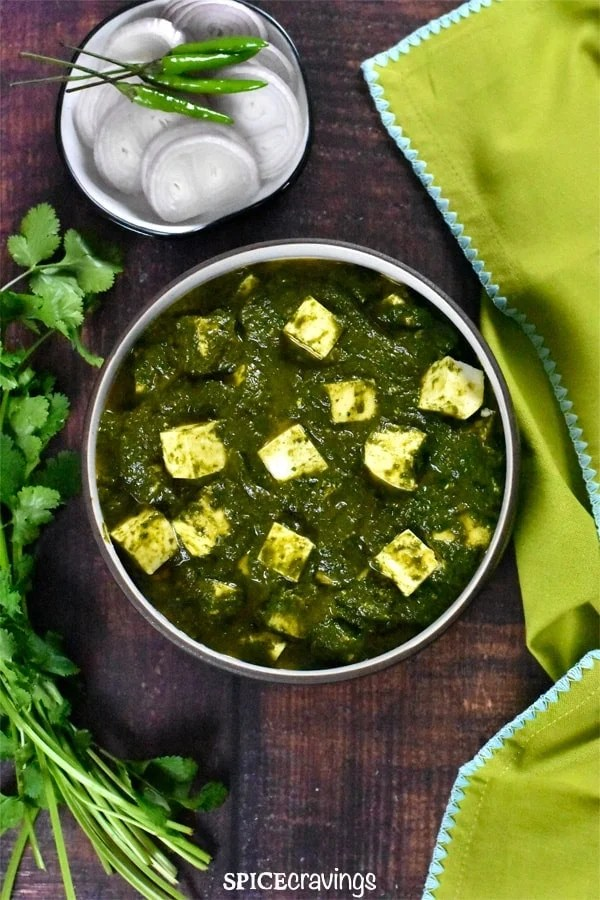 Palak paneer served with sliced onions.