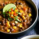 Black bean chili with corn and peppers, served with a wedge of lime