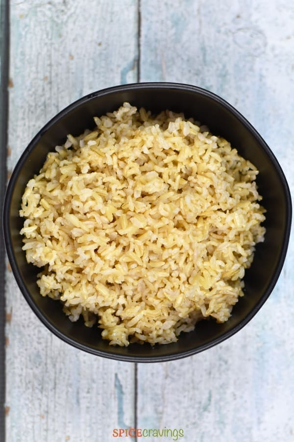 A black stone bowl full of brown rice on a blue wooden background