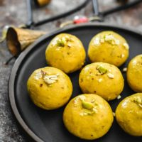 A plate of Besan Ladoo next to decorative bells