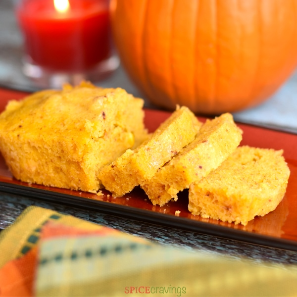 A sliced loaf of Pumpkin Spice Cornbread on a red serving tray