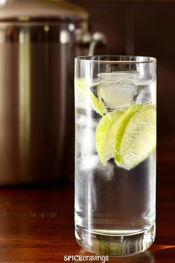 A tall glass of chilled gin tonic placed next to an ice bucket