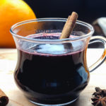 Mulled wine, or gluhwein, served in a glass cup, garnished with a cinnamon stick.