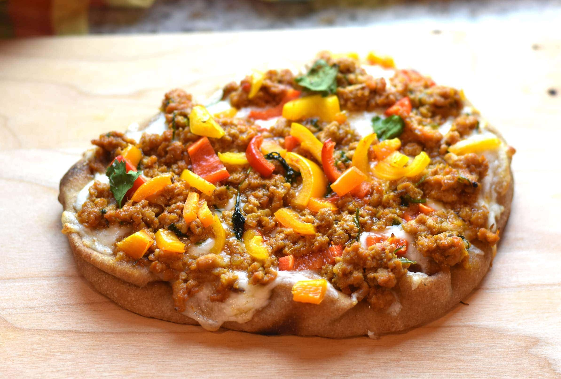 Indian Spiced Naan Pizza served on a wooden cheeseboard