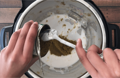 Adding store-bought green curry paste to the pot