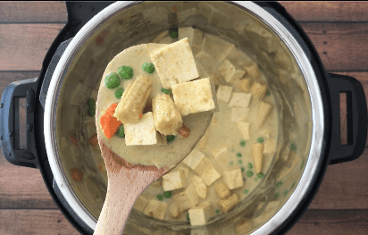 A wooden spoon with thai green curry with vegetables and tofu