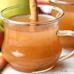 A cup of spiced apple cider with a cinnamon stick